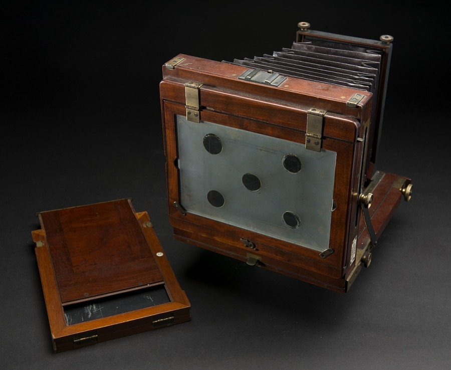 Back view of wooden box camera with black bellows and brass fittings, next to wooden                 photographic plate holder or dark slide