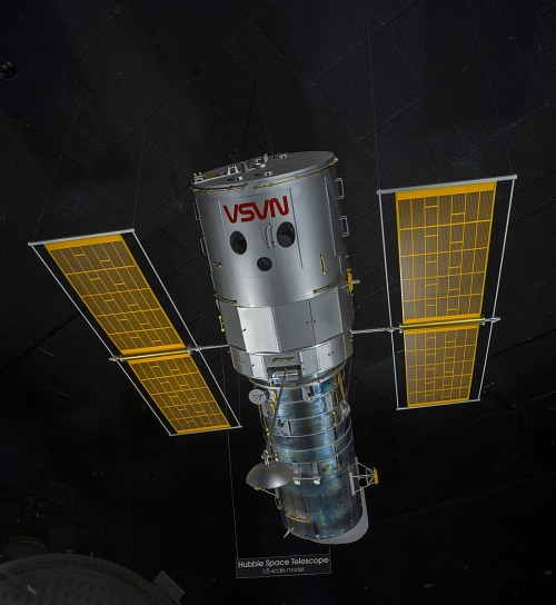 Overall view of the Hubble Space Telescope Model hanging in museum, with upside down NASA logo