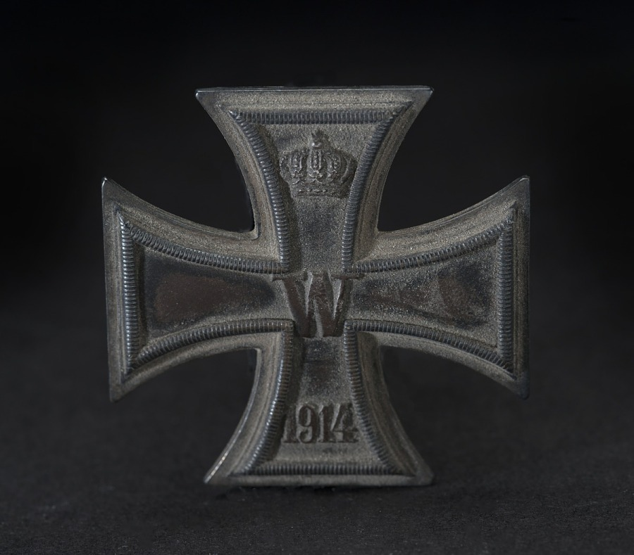 Metal pin in shape of a cross, with a crown in upper arm, 'W' in center, and 1914 in lower rm