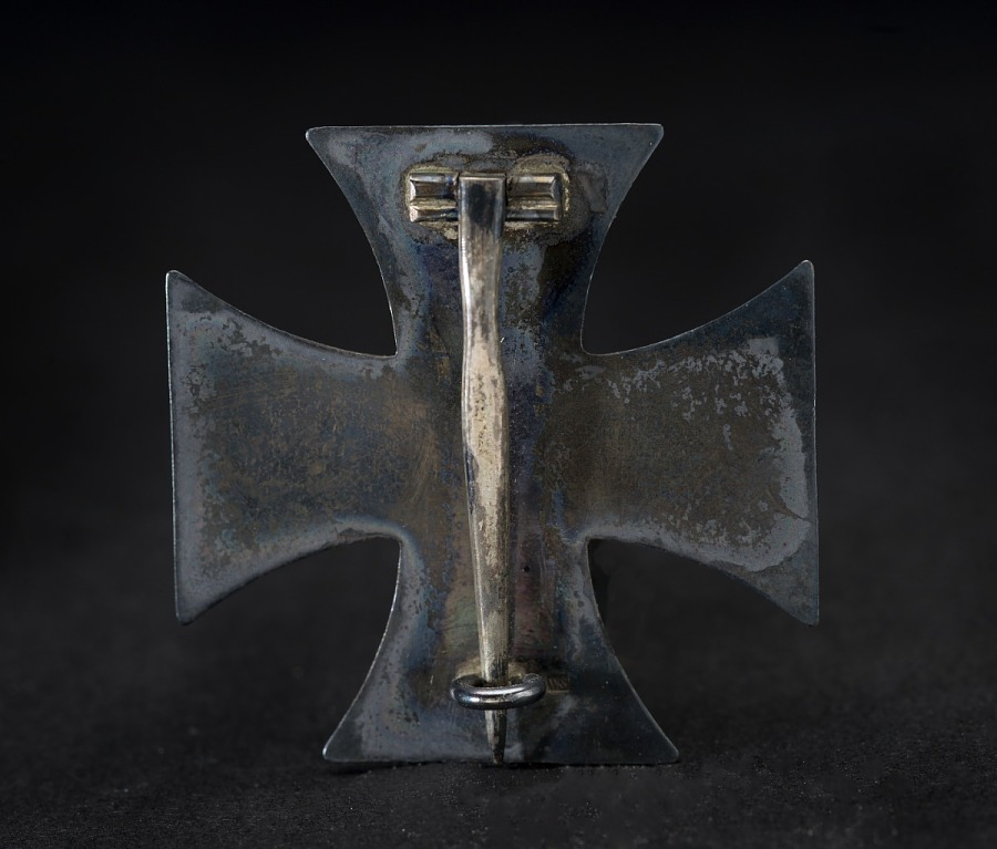 Back of medal in shape of a cross with pin on a vertical hinge