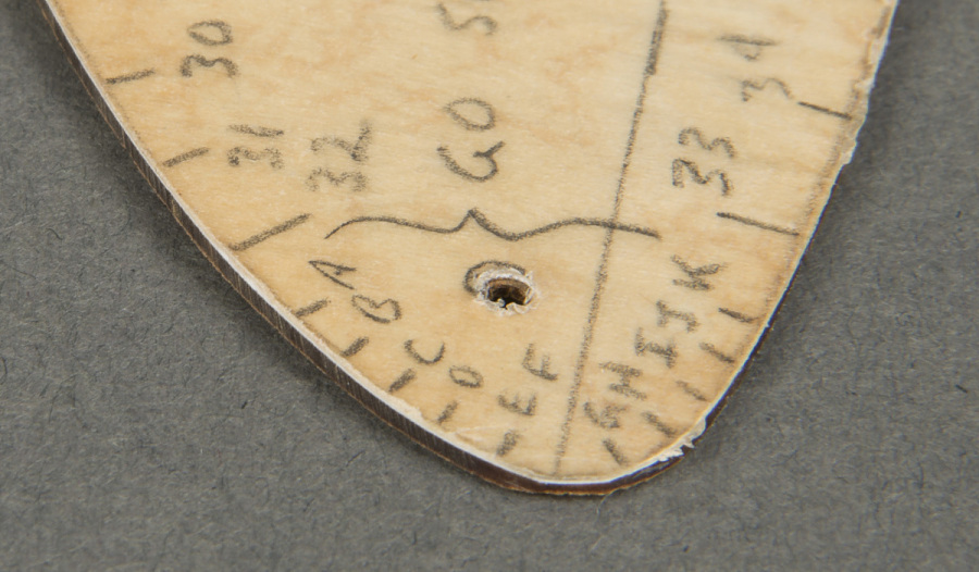 Tip of thin plastic wing-shaped Canard Template with alphabetical pencil markings