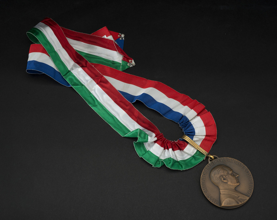Reverse of bronze commemorative medal with portrait of Count Caproni, on red, white, green, and                 blue striped ribbon
