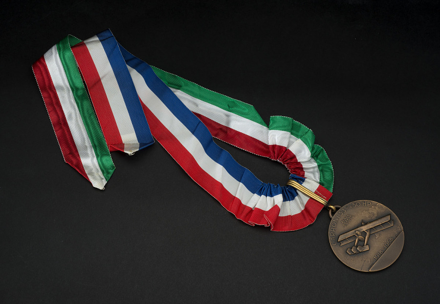 Bronze commemorative medal with image of Caproni bomber, on red, white, green, and blue striped                 ribbon