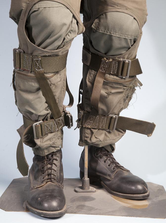 Olive green United States Navy Leg Restraint straps over pants on calves of mannequin legs