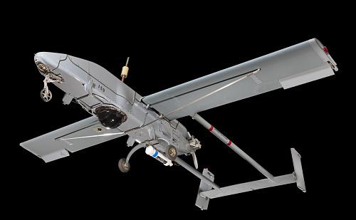 Bottom of slim, gray Pioneer RQ-2A UAV aircraft, against black background