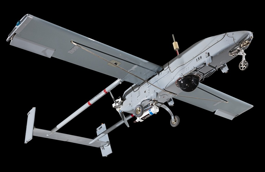 Bottom of slim, gray Pioneer RQ-2A UAV aircraft, against black background