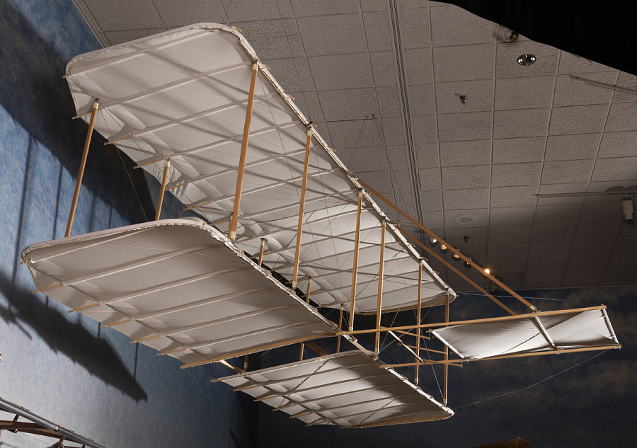 Underside view of full-size reproduction of fabric and wood glider, hanging in museum