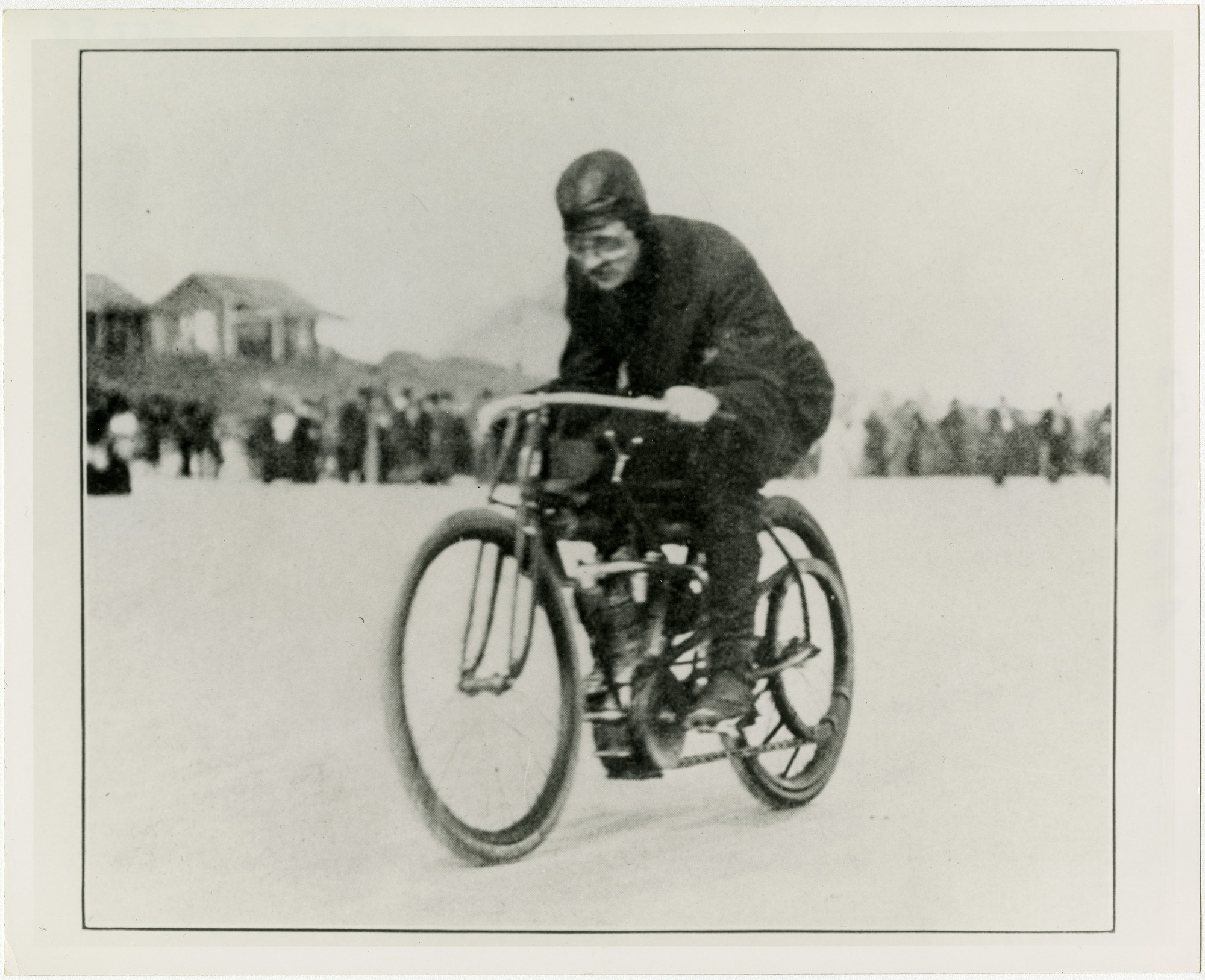Wearing a leather helmet, Glenn Curtiss hunches over the handle bars of his experimental motorcycle as he rides at record-breaking speeds, January 24, 1907.