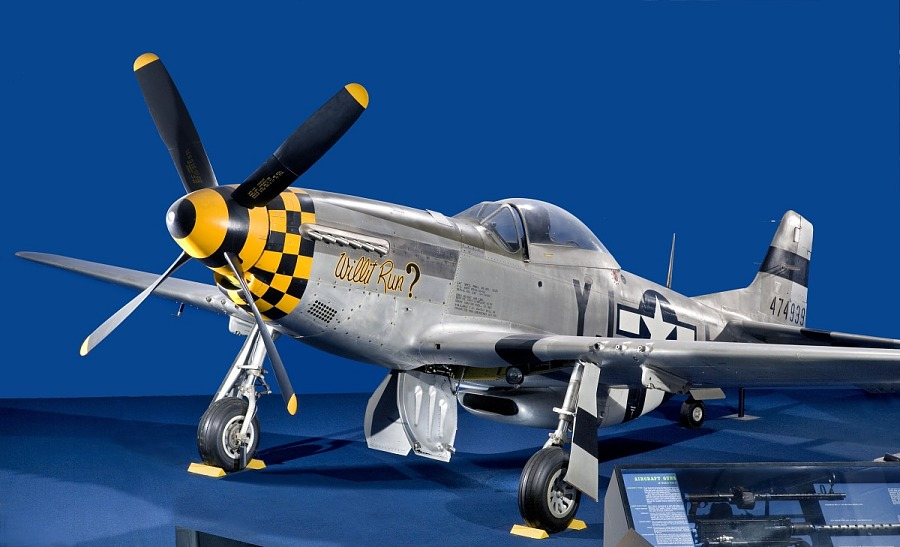 Gray and yellow checkered P-51 Mustang aircraft in museum display against a blue background