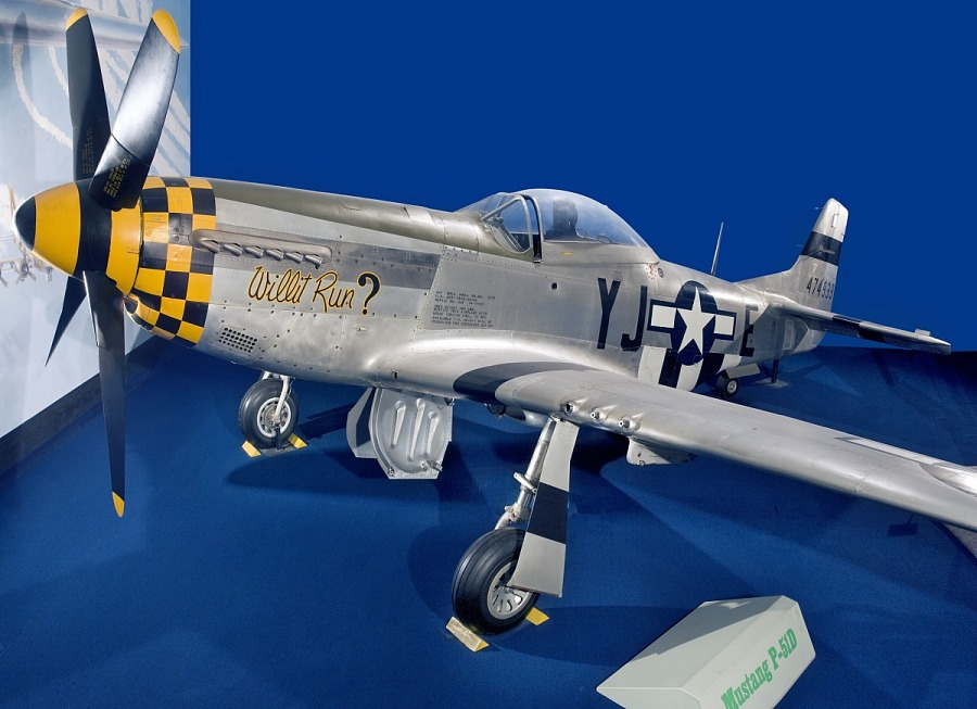 Gray and yellow checkered P-51 Mustang aircraft in museum display