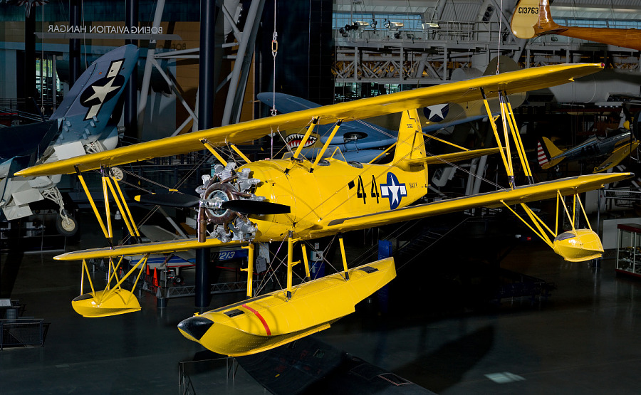 Bright yellow bi-plane with hand crank start hanging in the Steven F. Udvar-Hazy Center.