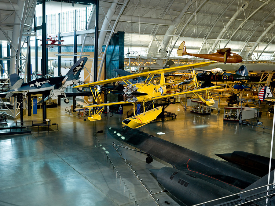 Yellow biplane hanging above the ground in museum