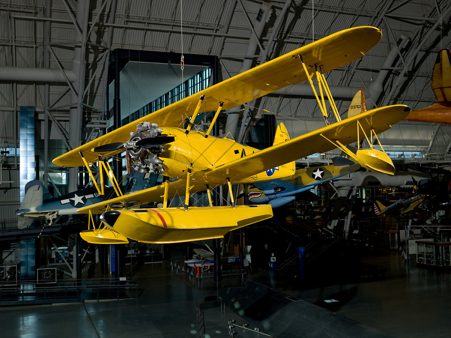 Angled view of yellow biplane hanging above the ground in museum