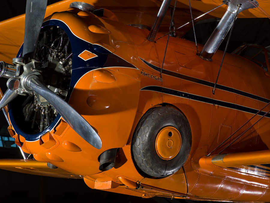 Image of landing gear and propellers of a orange painted aerobatic aircraft.