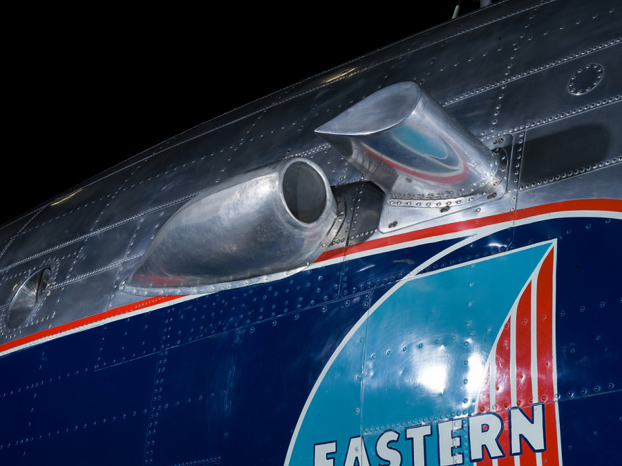 Close up of a silver painted exhaust valve on the fuselage of the plane.