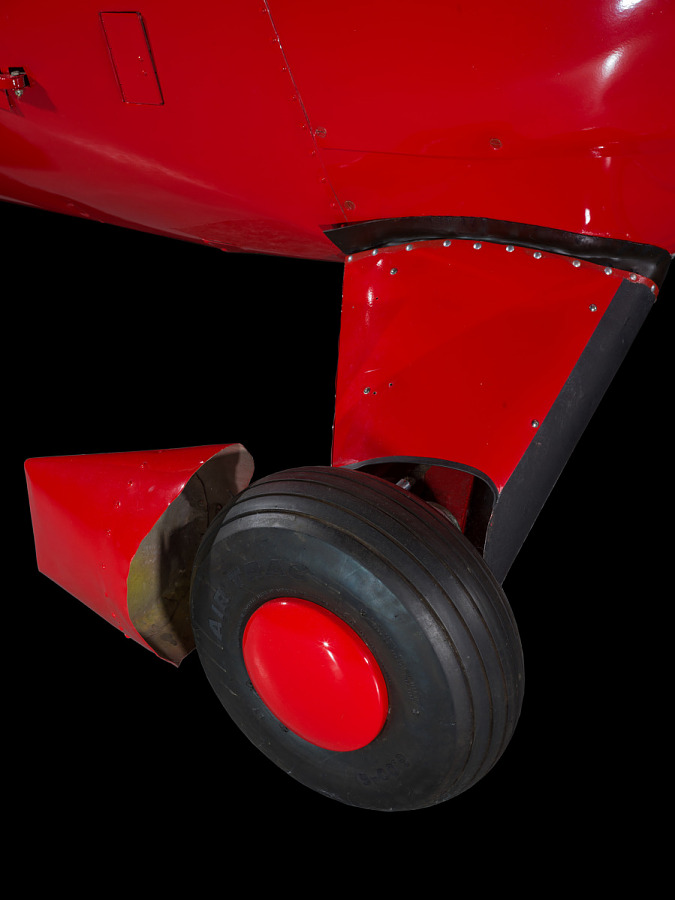 Close up of a tire and landing gear of a red painted plane.
