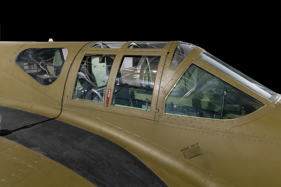Close up view of a cockpit of a green painted jet aircraft.