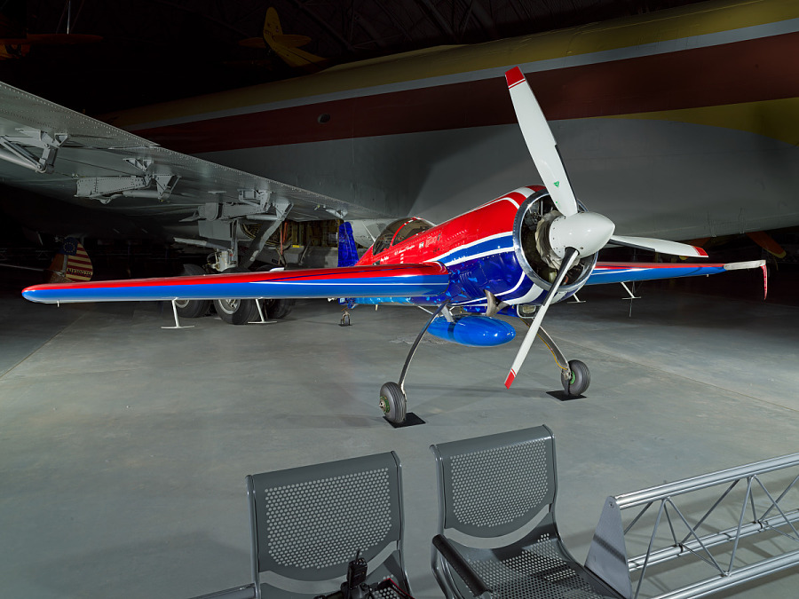 Frontal view of a red and blue plane. In front of the plane are two chairs.