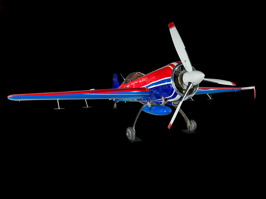 Red and blue painted plane. From this angle, you can see the propellers, landing gear, and fuselage of the plane.