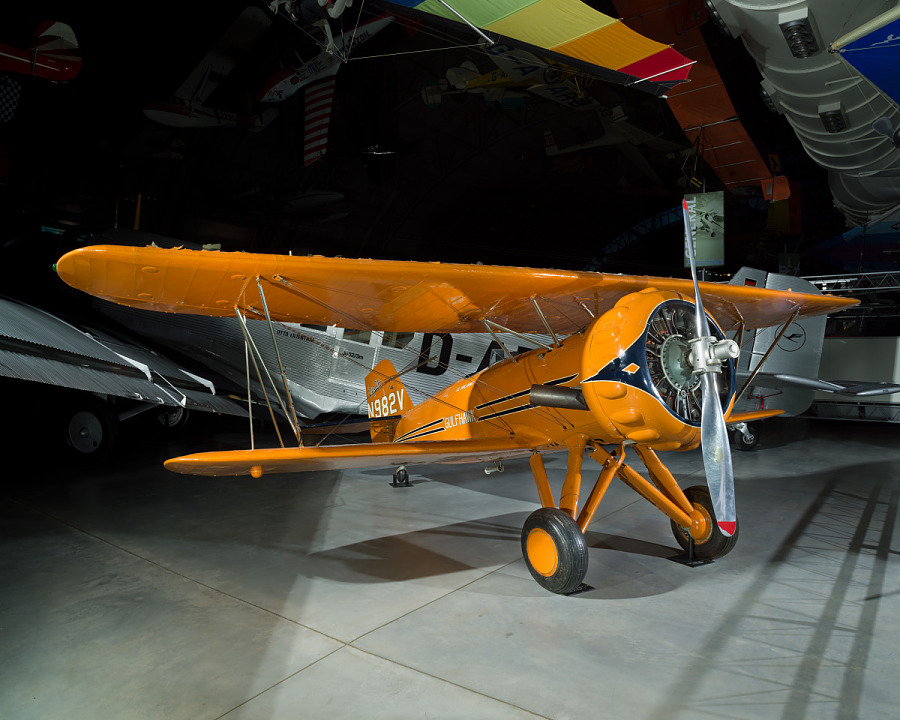 Orange painted biplane in the museum. Painted on the tail of the plane is N982V.