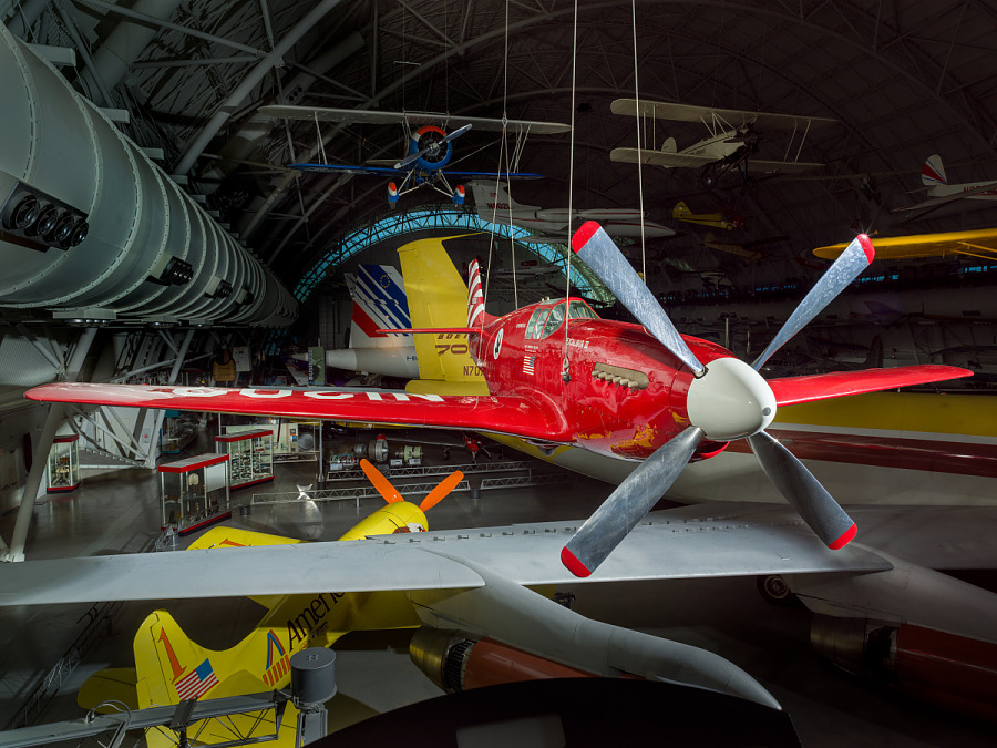 View of a red painted plane hanging in the museum.