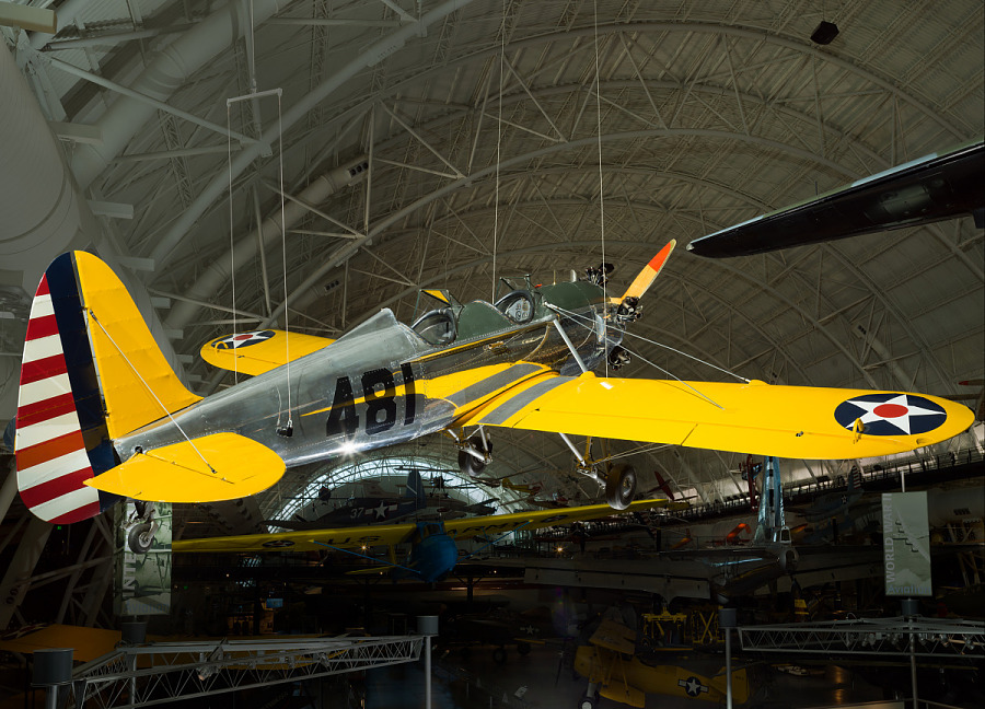 View of a silver and yellow painted plane hanging from the roof of the museum.