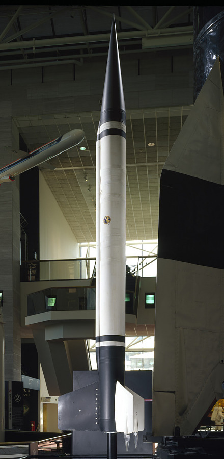 Tall, black and white cylindrical shaped rocket standing in museum