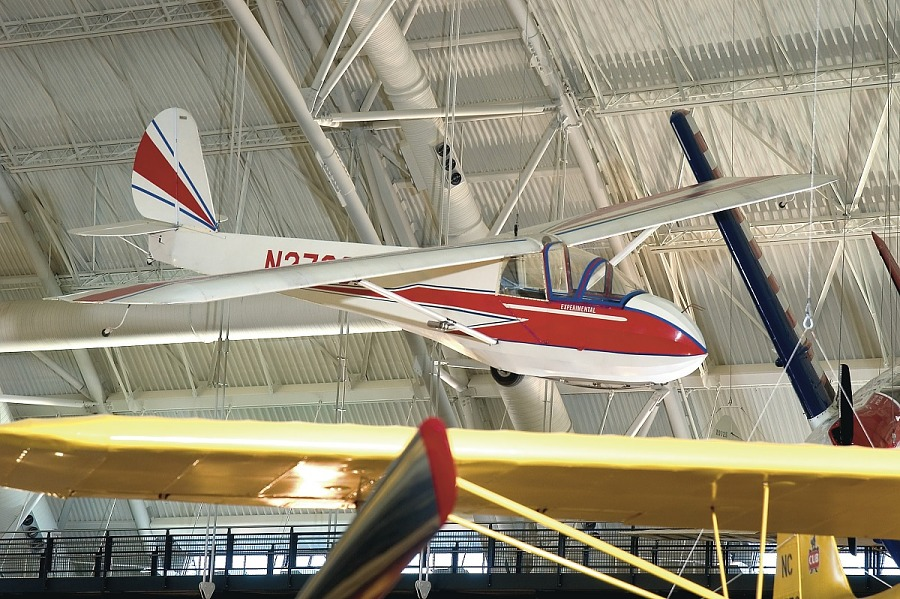 Right front view of red and white sailplane hanging in the museum