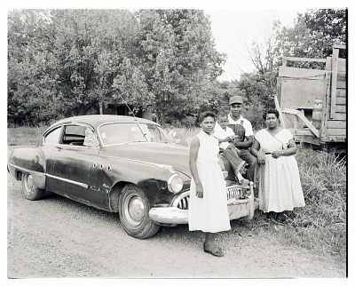 Outdoor Photo of Two Women with a Man and Child on the Hood of a Car