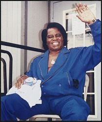 Photograph of James Brown sitting in a chair, waving with his left hand