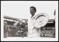 Photograph of Althea Gibson holding a Wimbledon trophy plate
