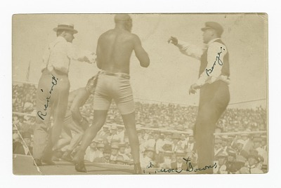 Photographic postcard of James J. Jeffries staggering away from Jack Johnson