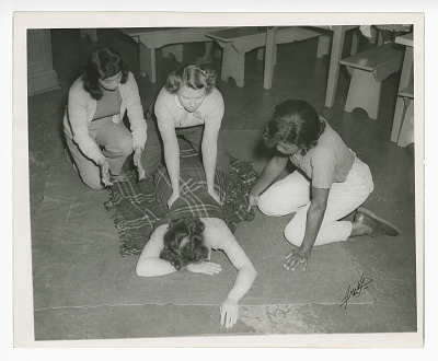 Photograph of four young women practicing first aid