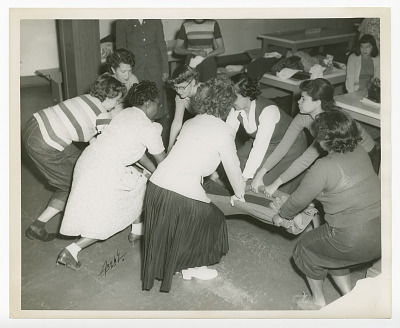 Photograph of young women practicing first aid