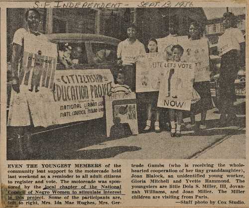 Image for News clipping of a photo of women and children with voter registration signs
