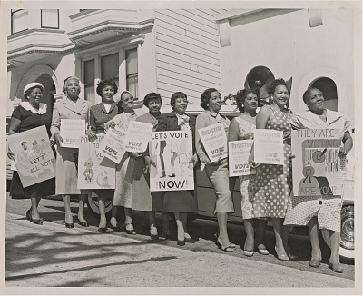 Photograph of women activists with signs for voter registration