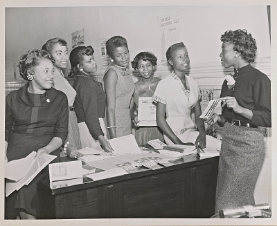 Photograph of seven Junior NCNW members with voter information pamphlets