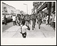 Image for Photograph of a boy walking ahead of soliders during the Newark Riots