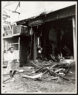 Image for Photograph of a girl walking in front of a looted store after the Newark Riots