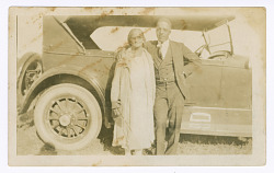 Photograph of a man and woman in front of car