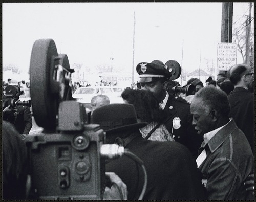 Image for Coretta Scott King is being protected by police officers and civil rights workers as she leaves Ebenezer Baptist Church