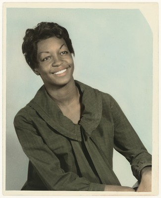 A hand-tinted photograph of a woman