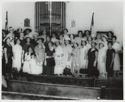 Group portrait of women posed in front of church organ