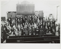 Group portrait of women posed in front of a church organ