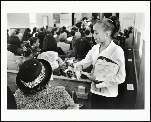 Image for Youth usher Vivica Brooks passes out fans to congregants during Deacons', Deaconesses', and Evangelists' ordination service at Righteous Church of God, Washington, D. C., 2003