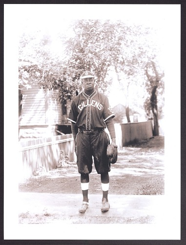 Image for Print of a man in a baseball uniform standing on the sidewalk