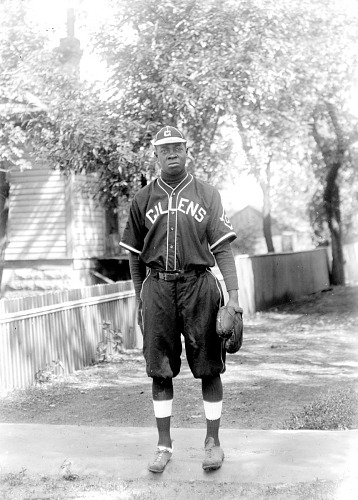 Image for Scan of a man in a baseball uniform standing on the sidewalk