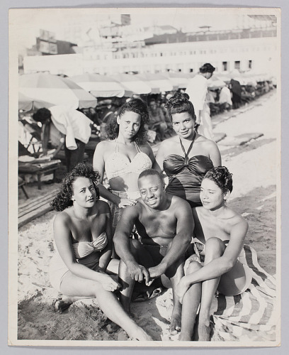 Image for Photograph of a man and four women sitting on a beach