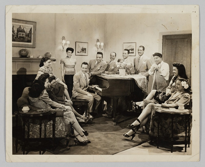 Image 1 for Photograph of a group of people gathered around a piano