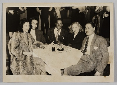 Photograph of three men and two women seated at a table